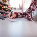 Frau mit dunkelrotem Elch-Pulli sitzt vor einem Weihnachtsbaum am Schreibtisch und schreibt Weihnachtskarten.