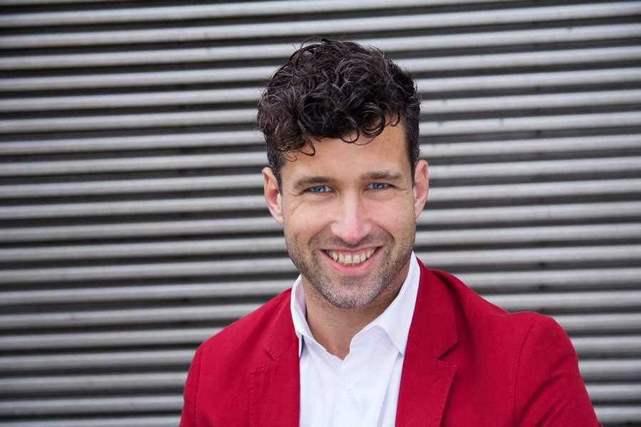 Kommunikationstrainer und Autor Patrick Nini in Hemd und rotem Sakko vor grauer Wand mit Querstreben
