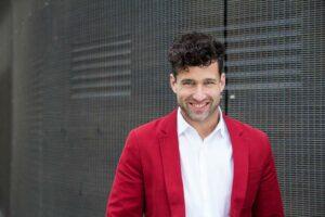 Kommunikationstrainer und Autor Patrick Nini in Hemd und rotem Sakko vor grauer Wand