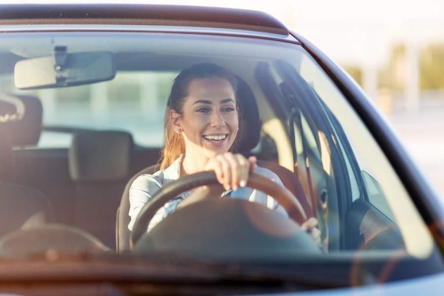 Eine junge Frau sitzt lächelnd und unbekümmert hinter dem Steuer Ihres Autos.