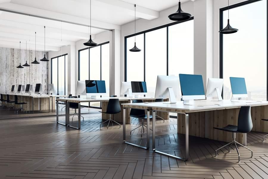 Gut beleuchteter und geräumiger Coworking Space vor Glasfront.
