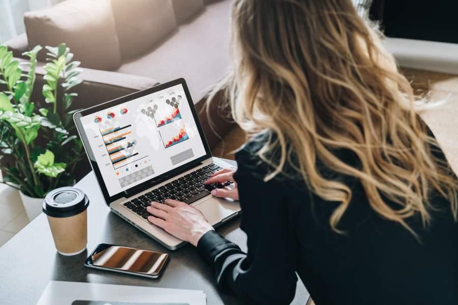 Junge Frau sitze vor ihrem Laptop, neben dem ein Coffee to go Becher und ein Smartphone liegen und werten verschiedene Daten und Statistiken aus.