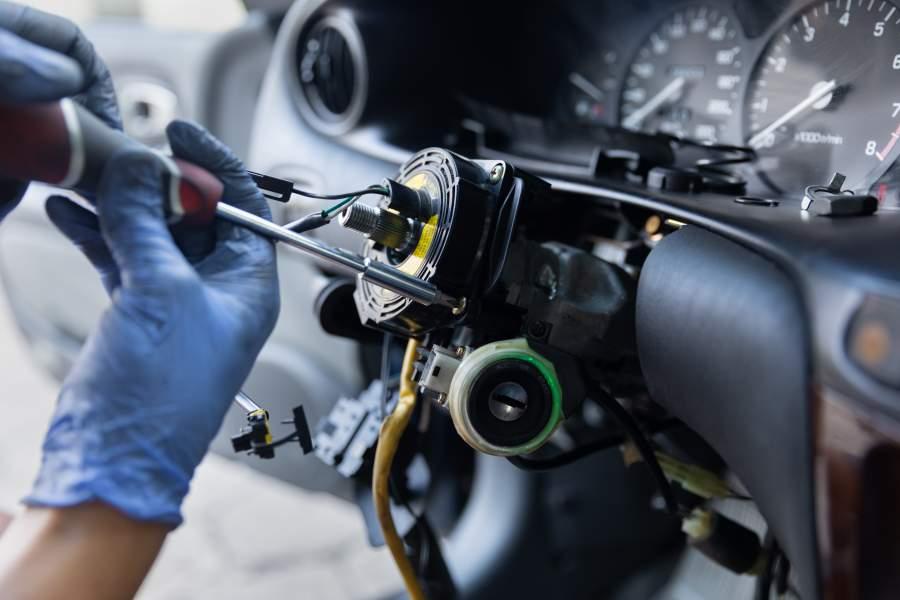 Close-up-Aufnahme von zwei Händen in Einmal-Handschuhen bei der Reparatur der Lenkradelektronik eines Autos
