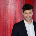 Buchautor und Kommunikationstrainer Patrick Nini in Hemd und Sakko vor roter Wand