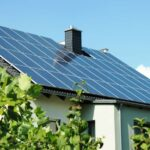 Einfamilienhaus mit Photovoltaik-Anlage mit grün belaubten Bäumen im Vordergrund.
