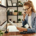 Junge Frau mit Brille in Business-Outfit an Schreibtisch telefoniert und blickt auf Unterlagen in ihrer Hand