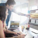 Zwei Personen an einem Schreibtisch diskutieren Aufbau und Gestaltung einer Webpräsenz