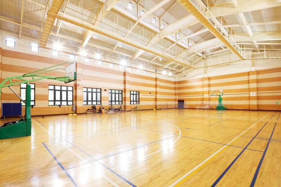 Eine helle, lichtdurchflutete und moderne Sporthalle mit Basketballkörben.