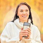 Junge Frau hält gut gelaunt einen wiederverwendbaren Coffee to go Becher in der Hand