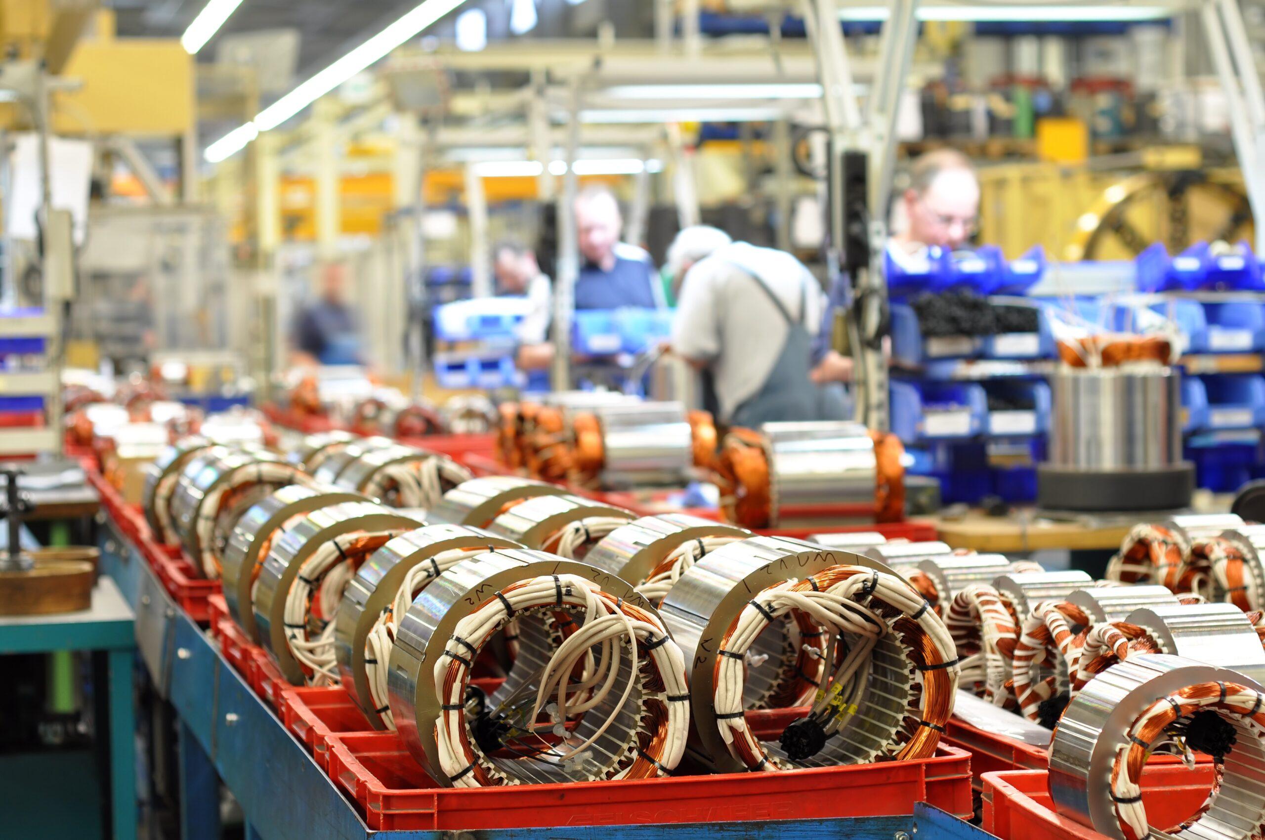 Mehrere Männer beim Arbeiten an Maschinen in einer großen Industriehalle.