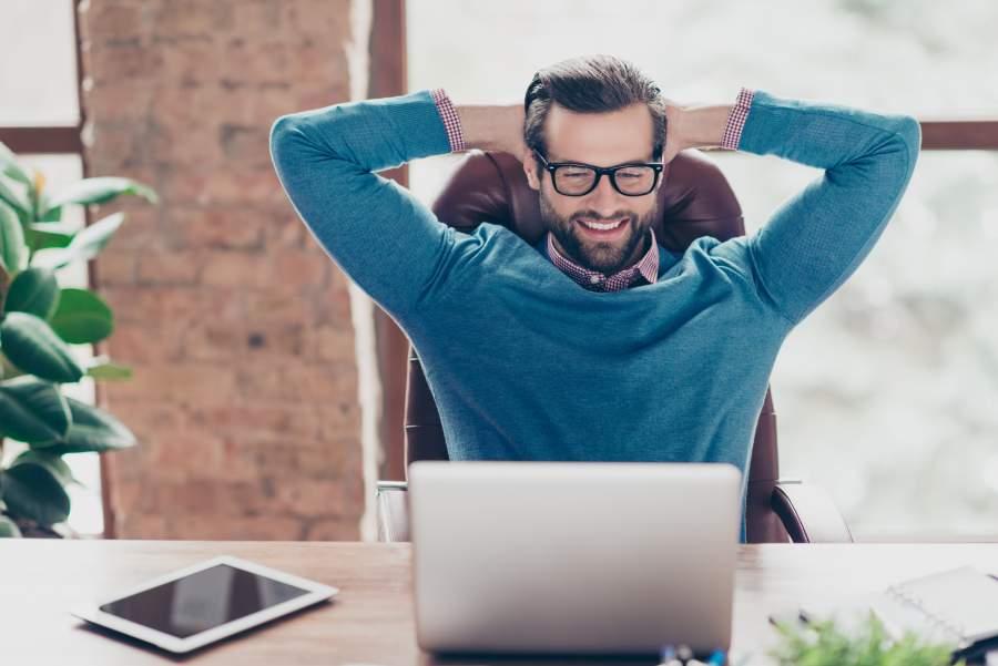 Mann im Casual Business Outfit sitzt entspannt am Schreibtisch mit Laptop und Tablet mit den Armen hinter dem Kopf