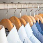 Von hell nach dunkel sortierte Anzughemden, die auf Holzbügeln an einer Kleiderstange hängen.