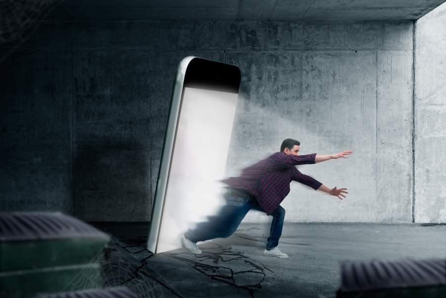 Mann flüchtet aus einem riesigen leuchtenden Smartphone-Screen in eine Straße.
