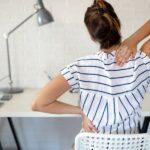 Frau sitzt mit dem Rücken zur Kamera an einem Schreibtisch und hält sich den Rücken vor Schmerzen.