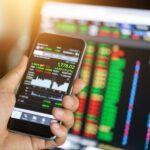 Eine Hand hält ein Smartphone vor einem Laptop auf die Höhe, während auf beiden Geräten Interaktionen des Online-Tradings zu sehen sind.