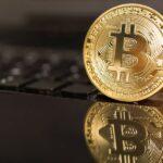 Physische Silber-Münze mit Bitcoin-Zeichen steckt zwischen den Tasten eines schwarzen Laptops und spiegelt sich in dessen Oberfläche.