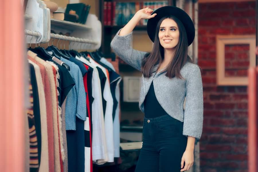 Eine junge, hübsche Frau steht in einem angesagten Fashion-Store und probiert einen Hut an.