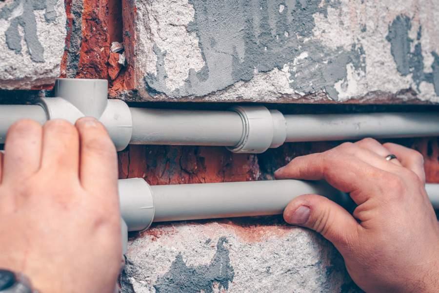 Mann arbeitet gerade an offengelegten Wasserleitungen in einer Wand.
