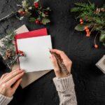 Frau schreibt weihnachtliche Grußkarten während neben ihr verschiedene Bastmaterialien wie Paketschnur, Tannenzweige und getrocknete Beeren liegen.