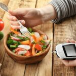 Portion Salat, die mit einer Gabel gegessen wird, in der anderen Hand ein Blutzuckermessgerät