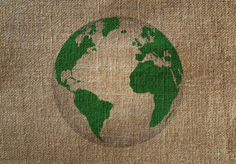 Grüner, stilisierter Druck des Erdballs auf grob gewebtem Jutestoff.