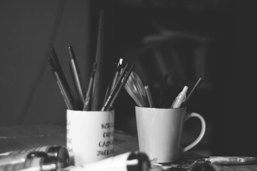 In zwei weißen Tassen, die als Stiftebechern benutzt werden, stecken verschiedene Stifte wie Kugelschreiber und Feinliner.