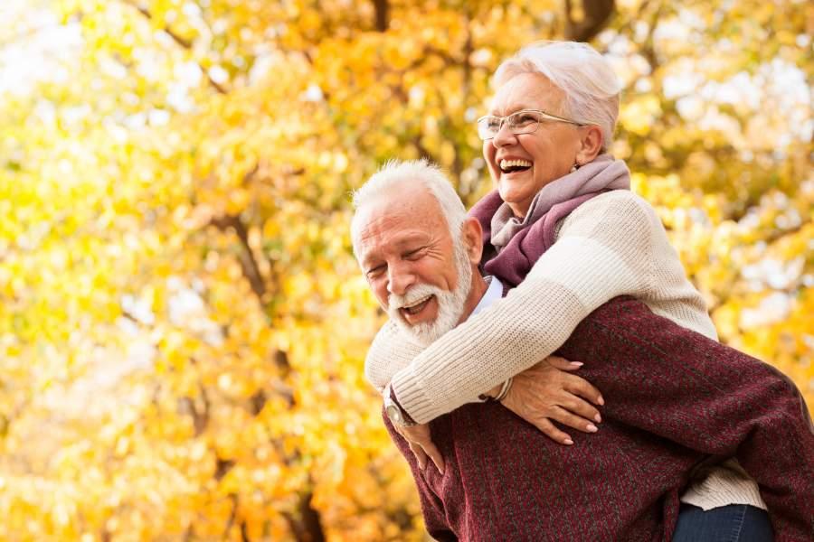 Älteres, lachendes Paare, das im goldenen Herbst draußen im Freien ist, während der Mann seine Frau Huckepack nimmt.