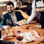 Mehrere Geschäftsmänner, die bei einem Geschäftsessen in einem Sushi-Restaurant sitzen und gerade bedient werden.