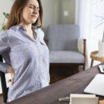 Junge Frau sitzt an Ihrem Schreibtisch und hält sich vor Schmerzen den unteren Rücken.