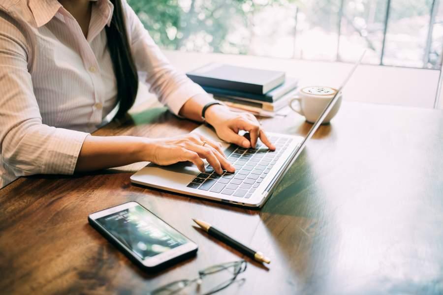 Junge Frau arbeitet an einem Laptop an einem Holztisch, auf dem Smartphone, Brille, Stift, Cappuccino-Tasse und Bücher zu sehen sind