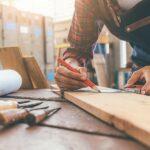 Ein Schreiner in einer Werkstatt zeichnet mit einem Bleistift gerade etwas auf einem Holz an, das auf einer Werkbank neben verschiedenen Werkzeugen liegt.