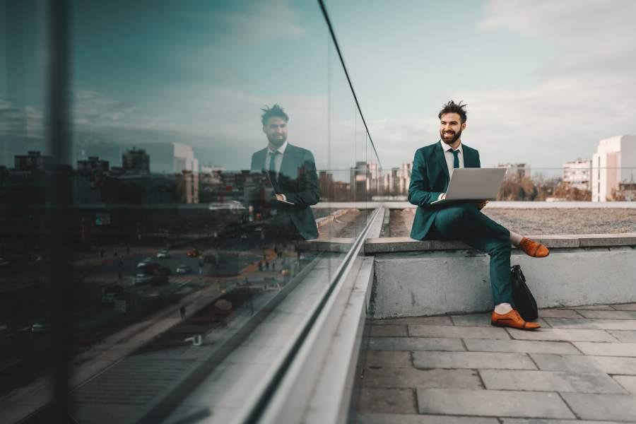 Geschäftsmann in Anzug sitzt lässig auf einem Hochhausdach mit Blick über die Start und arbeitet auf seinem Laptop.