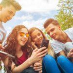 Gruppe von Jugendlichen mit Smartphones in den Händen sitzen gemeinsam im Freien und sehen sich gemeinsam auf dem Smartphone eines der Mädchen etwas an.