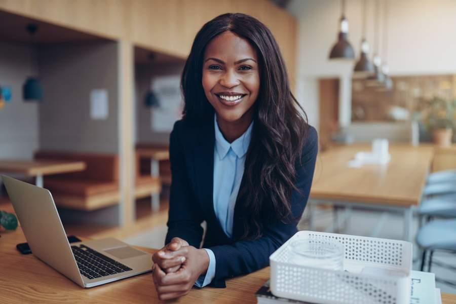 Eine afroamerikanische Geschäftsfrau in Businessoutfit, die mit einem breiten Lachen an einem Schreibtisch sitzt.