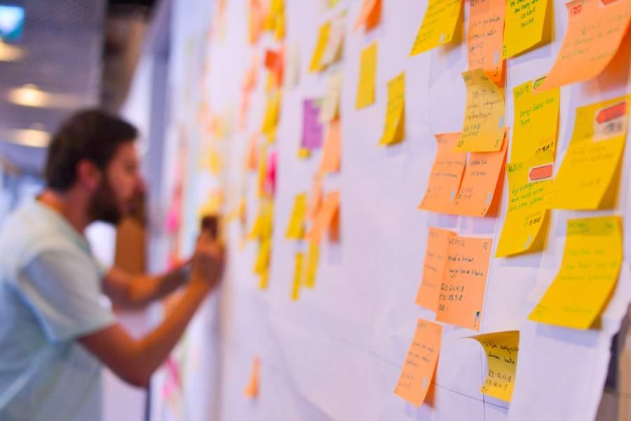Mann in agiler Zusammenarbeitsstruktur aktualisiert ein Kanban Board mit vielen Klebezetteln in Gelb- und Orange-Tönen