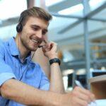 Junger Mann telefoniert lächelnd mit aufgesetzten Kopfhörern in einem modernen Büro.