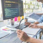 Mehrere Programmierer arbeiten in einem modernen Büro an einem Schreibtisch, auf dem mehrere Bildschirme stehen.