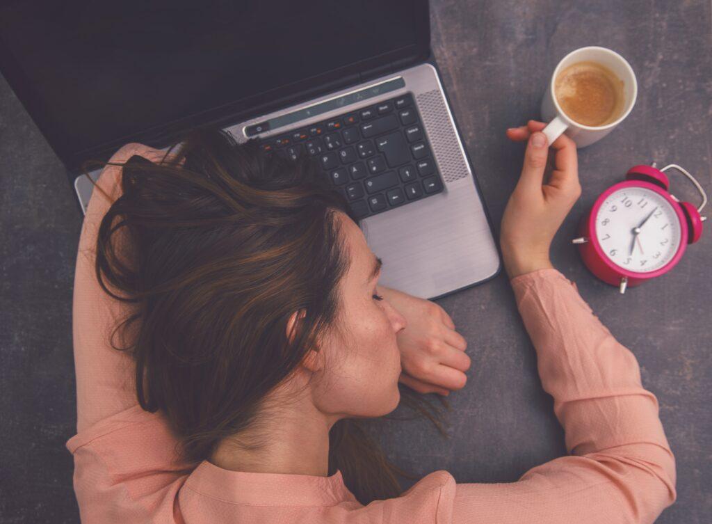 Frau in rosa Pulli schläft mit einem Kaffee in der Hand auf ihrem Laptop, neben dem ein analoger Wecker liegt.