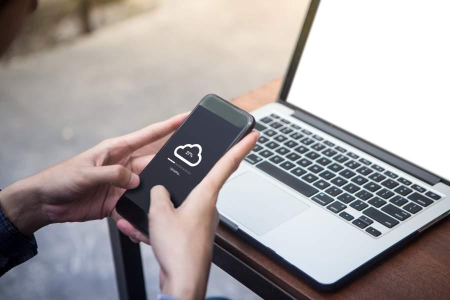 Hände halten ein Smartphone mit Cloud-Upload-Anzeige, im Hintergrund ein Laptop mit weißem Screen