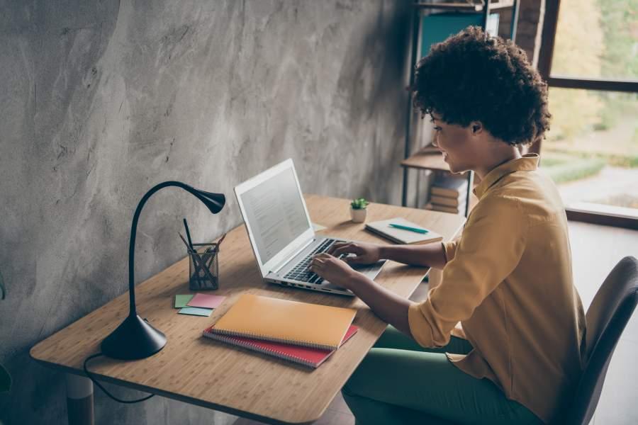 Junge afroamerikanische Frau in senffarbener Bluse sitzt in einem modernen Arbeitszimmer an einem Laptop, neben dem ein Block und Hefte liegen.