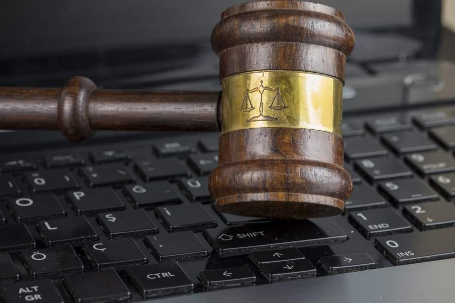 Ein hölzerner Richterhammer mit Prägung einer Waage auf einer Computertastatur