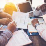 Diverse Menschen am Meeting-Tisch besprechen Unterlagen und Bilanzen