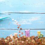 Gießkanne schüttet Geldmünzen auf weitere Münzen und Geldscheine (Euro) aus vor einem türkis-farbenem Hintergrund