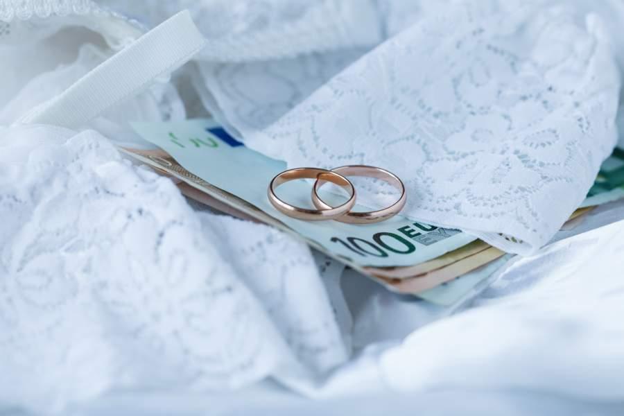 Verlobungsringe oder Eheringe drapiert auf Geldscheinen mit weißer Wäsche (Traditionell zur Hochzeit)