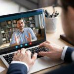 Virtuelles Business-Meeting zwischen zwei Geschäftsmännern, ein Mann im Homeoffice ist auf dem Laptop-Screen