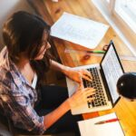 Vogelperspektive auf eine junge Frau, die am Laptop schreibt und vor dem Fenster sitzt, neben dem Laptop befinden sich Unterlagen, Zeichenmaterial, Pläne und eine Lampe