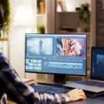 Junger Mann sitzt an Rechner mit zwei Bildschirmen und arbeitet an einer Videoproduktion