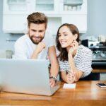 Junges Paar in hellem Raum lächeln und blicken auf einen Laptop-Screen mit Business-Transaktionen