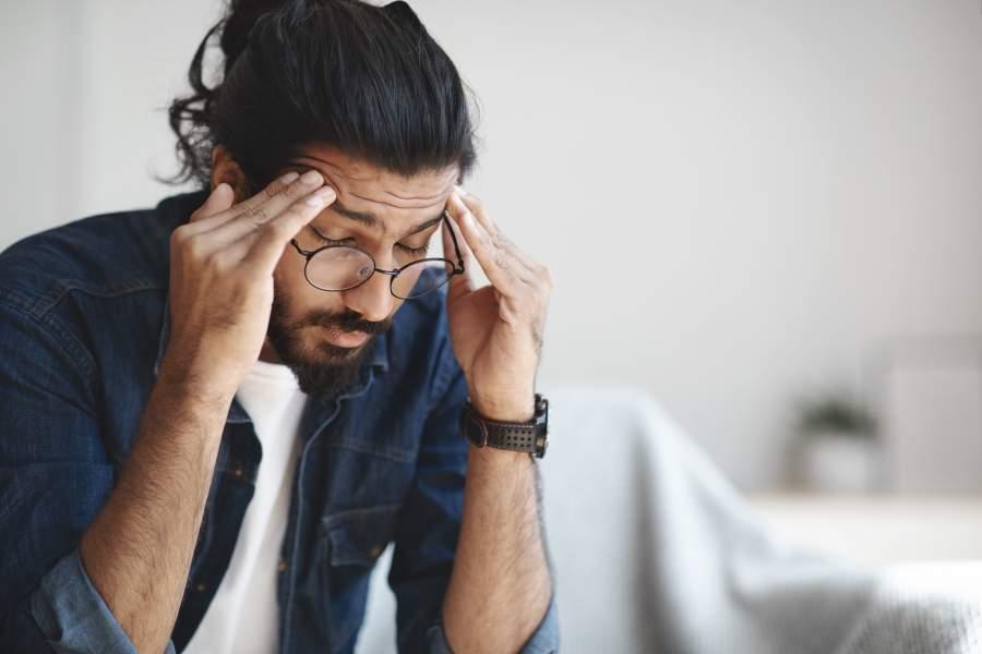 Junger Mann mit langen Haaren, Bart und Brille massiert sich die Schläfen und sieht sehr müde und erschöpft aus