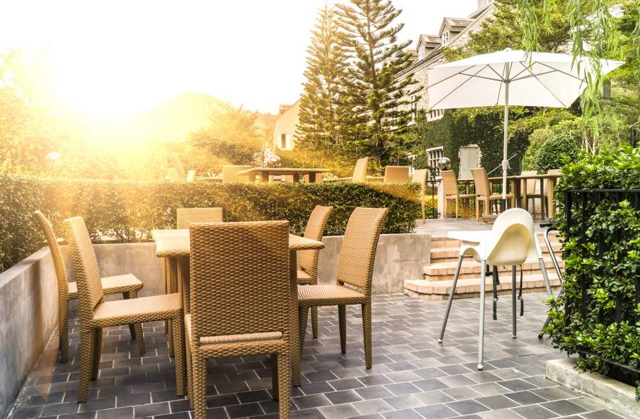 Gemütliche Rattanmöbel-Garnitur und Sonnenschutz umgeben von Hecken als Sichtschutz, tief stehende Sonne